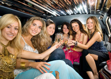 Group of beautiful women clinking glasses with champgagne inside a limousine 免版税图像
