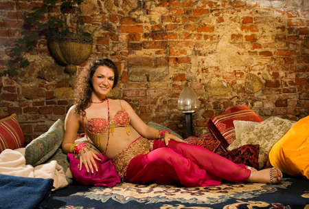 Beautiful woman in arabic costume sitting on pillows photo