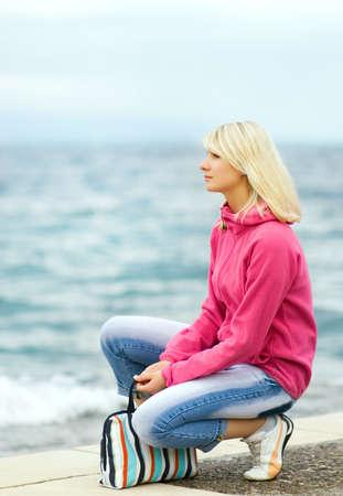 Sad woman sitting near the ocean photo