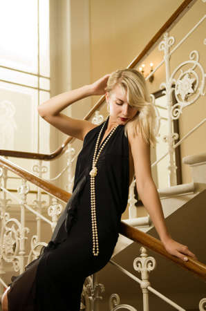 Beautiful young woman standing on a staircase photo