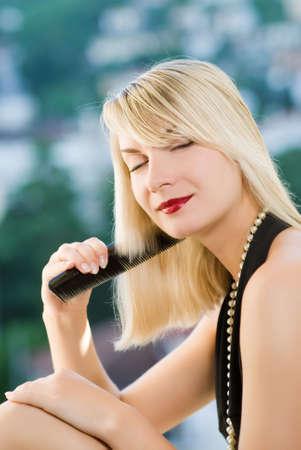 Beautiful young woman combing her hair Stock Photo - 3262823