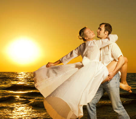 emotional couple: Beautiful young couple dancing on the beach at sunset