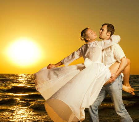parejas sensuales: Hermosa joven pareja de baile en la playa al atardecer  Foto de archivo