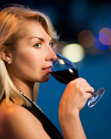 Beautiful young lady drinking red wine photo