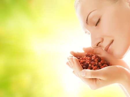 punhado: Beautiful young woman with handful of fresh strawberries