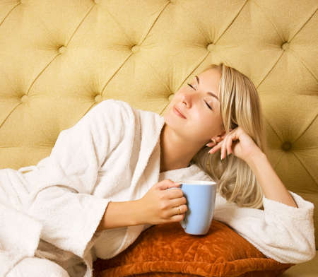 Bautiful young woman sitting on a bed and drinking cofee in the morning photo