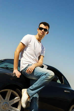 Young handsome guy near the sport car photo