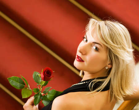 Beautiful young woman standing on a red carpet and holding a rose photo