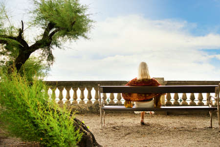 Young woman sitting on a bench in park Stock Photo - 3334357