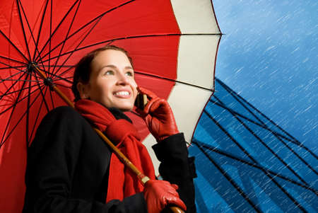 Beautiful brunette with red umbrella talking on the phone photo