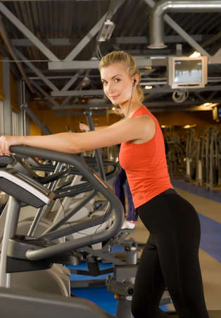 Beautiful young woman doing exercise in a gym while listening to music photo