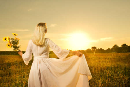Beautiful woman with sunflowers in the field at sunset photo