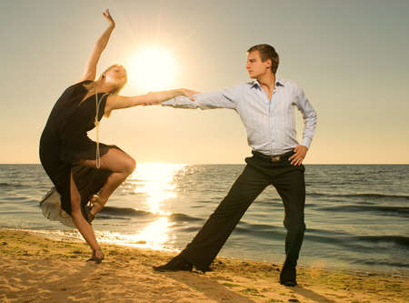 Beautiful young couple dancing tango on the beach at sunset photo