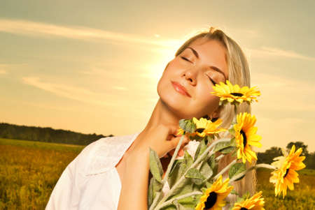 Young beautiful woman with a bouquet of sunflowers in the field at sunset photo