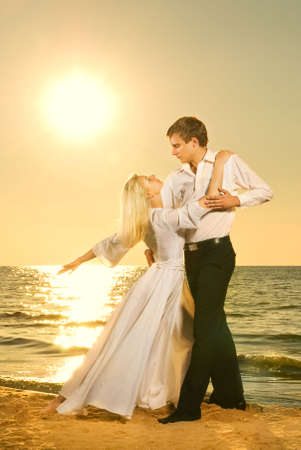 Young couple dancing on a beach at sunset photo