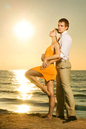 Young couple in love near the ocean at sunset Stock Photo - 3377235