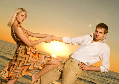 Young couple dancing near the ocean at sunset Stock Photo - 3377237