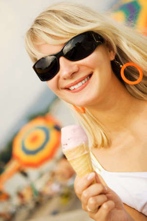 Beautiful young woman eating ice-cream on the beach photo