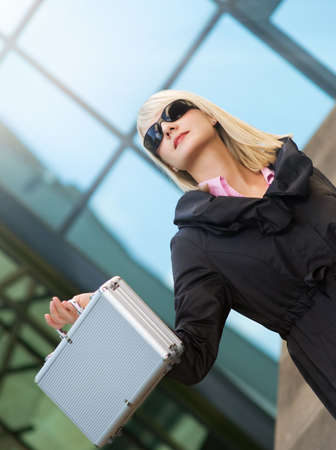 Beautiful young woman with silver case near the modern office building Stock Photo - 3386870