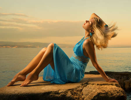 Sexy young woman flapping her blond hair near the ocean