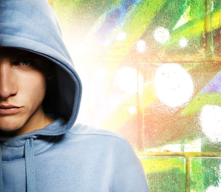 vandal: Cool looking man in a hood over abstract graffity background Stock Photo