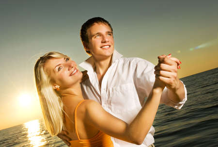 Young couple dancing near the ocean at sunset photo