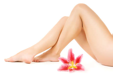 Female legs with pink lily isolated on white background Stock Photo