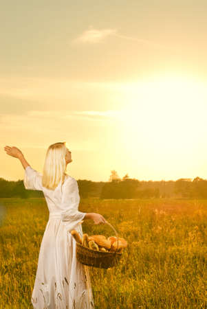 Woman with a basket full of fresh baked bread at sunset photo