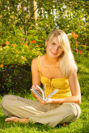 Happy young woman readin book in a park photo