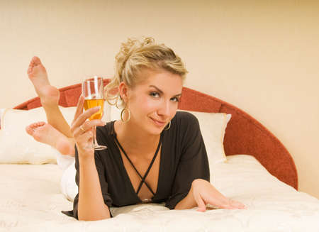 Beautiful young lady lying in a bed with a glass of champagne Stock Photo - 3463542
