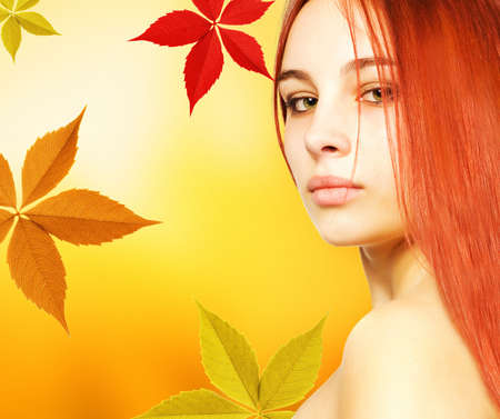 Beautiful young woman over abstract autumn background photo