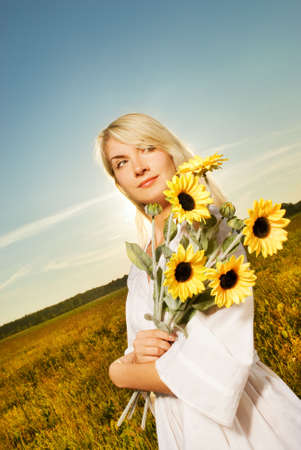 Young beautiful woman with a bouquet of sunflowers in the field photo