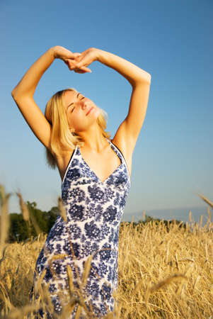 Beautiful blond girl stretching in the wheat field photo