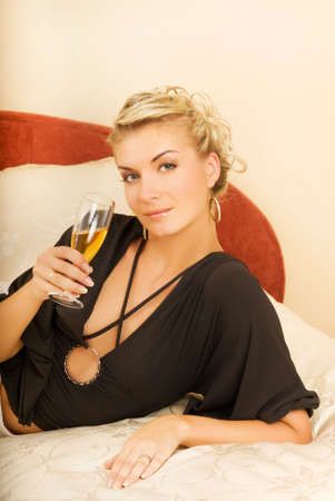 Beautiful young lady lying in a bed with a glass of champagne Stock Photo - 3479282