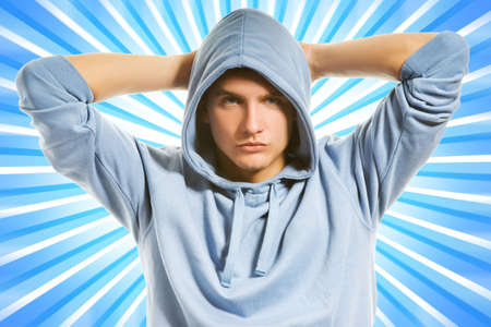 Handsome young man in a hood over abstract blue background photo