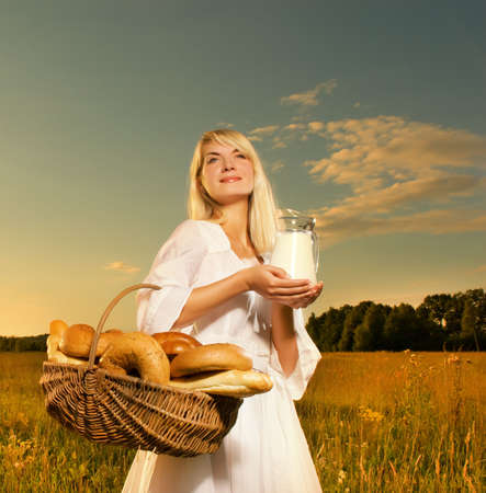 Beautiful young woman with a basket full of fresh baked bread and jug of milk photo