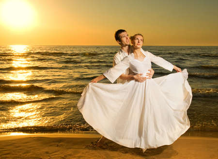 Young couple in love near the ocean at sunset photo