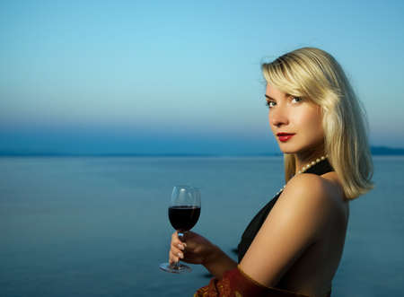 Beautiful young woman drinks red wine near the ocean photo