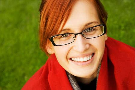 Beautiful young redhead woman relaxing outdoors photo