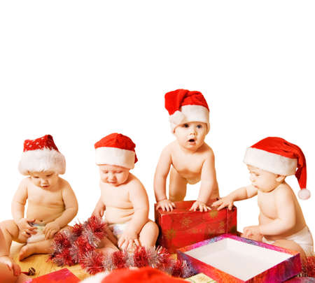 Group of adorable toddlers in Christmas hats packing presents. Isolated on white background photo