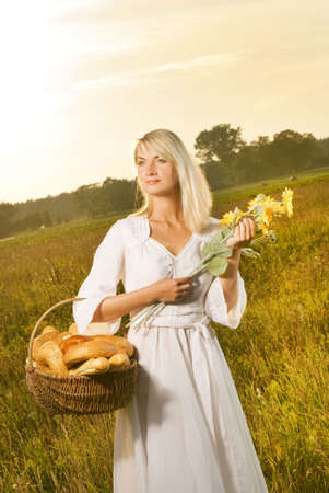 Beautiful young woman with a basket full of fresh baked bread photo