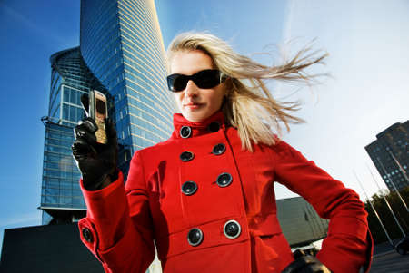 Beautiful young blond talks on the phone. Modern building behind her photo