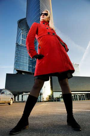 Joven y bella mujer rubia al aire libre. Moderno edificio detrás de ella