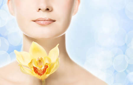 Beautiful woman with yellow orchid over abstract blue background Stock Photo - 3652876