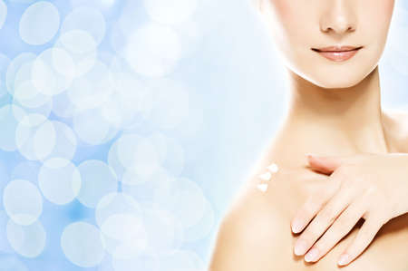 Young beautiful woman applying moisturizer to her skin after shower Stock Photo