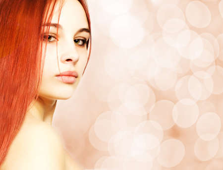 Beautiful redhead woman over abstract blurred background photo