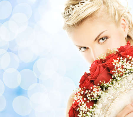 Beautiful bride hiding behind luxury bouquet of roses photo