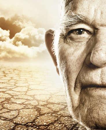 Elderly mans face over dry desert land background photo