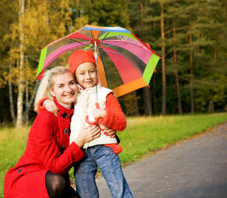 Mother and daughter in autumn forest photo
