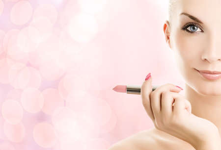Beautiful young woman with lipstick over abstract pink background photo